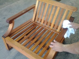 a man refinishing a wooden teak lawn chair with a cloth