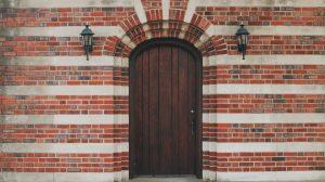 oak front door set in a multicolored brick home